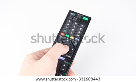 Hand holding or pressing button on remote controller for TV or media device. Isolated on white background. Slightly de-focused and close-up shot. Copy space. - stock photo