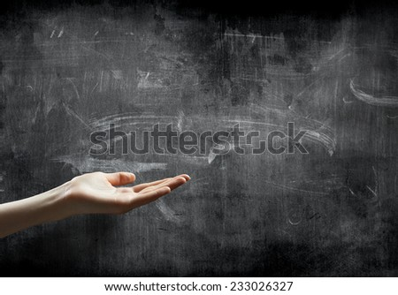 hand holding or showing your product in front of blackboard with copy space - stock photo