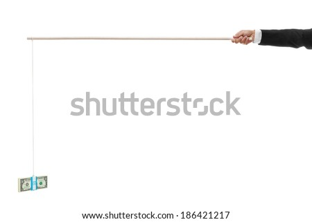 Hand holding out a stack of money tied to the end of a stick for bribery with copy space - stock photo