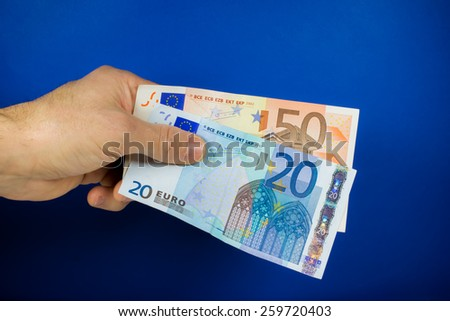 hand holding out two banknotes, on a blue background - stock photo