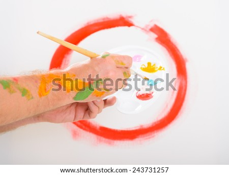 Hand holding paintbrush with artist palette, canvas on easel in a background - stock photo