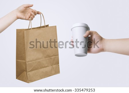 Hand holding paper bag and cup for your design presentation - stock photo