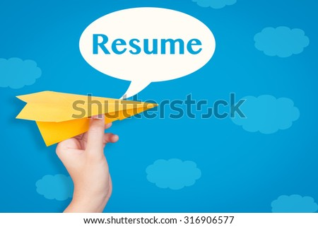 hand holding paper plane with resume text in speech bubble on blue background  - stock photo