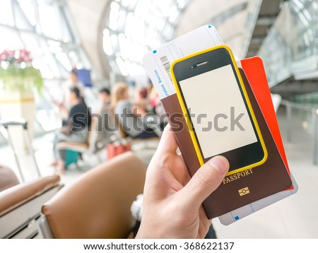 Hand holding passport, boarding pass and smart phone in airport in concept of going abroad - stock photo