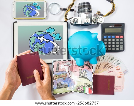 Hand holding passport book planning for dream destination  over piggy bank background/ traveling saving concept - stock photo