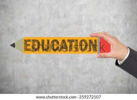 hand holding pencil with education text - stock photo