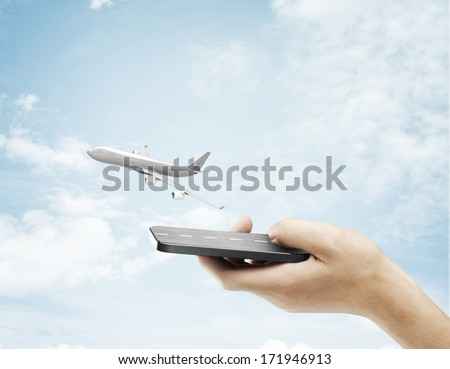 hand holding phone and airplane in sky - stock photo