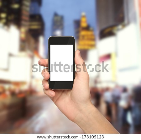 hand holding phone in city - stock photo