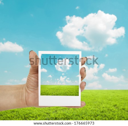 Hand holding photograph of landscape with landscape in background - stock photo