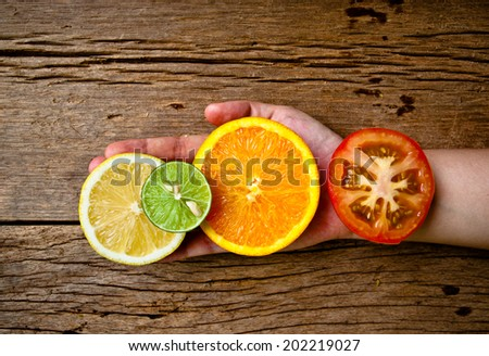 Hand Holding (Pick,Select) Half Cut Sliced Group of Citrus Fresh Lemon, Green Lime, Orange and Red Tomato on Wood Table Background, Rustic Still Life Style. / Concept and Idea of Food Decoration. - stock photo