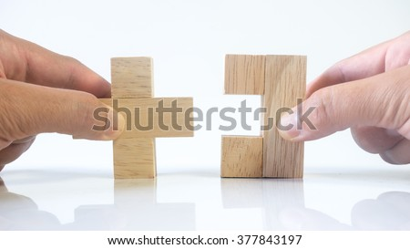 Hand holding piece of wooden block puzzle. Isolated on empty background. Concept of complex and smart logical thinking. Slightly defocused and close up shot. Copy space. - stock photo