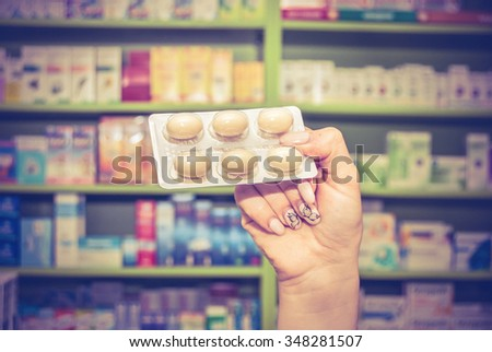 Hand holding pill out from blister pack. Medicine.. toned photo - stock photo