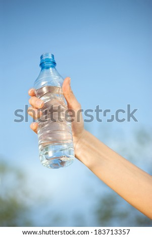 hand holding plastic bottle of water in front of sky - stock photo