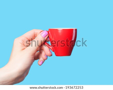 Hand holding red cup on blue background - stock photo