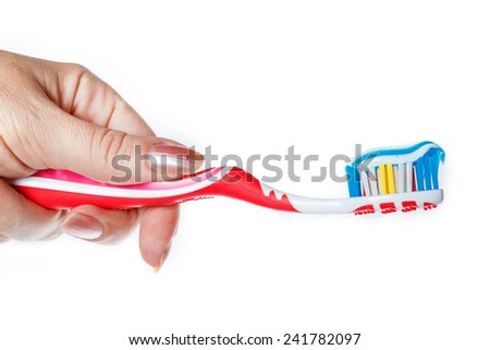 Hand holding red toothbrush with blue two color toothpaste on light surface. Photo of dental hygiene and health maintenance. Object isolated on white background without shadows - stock photo