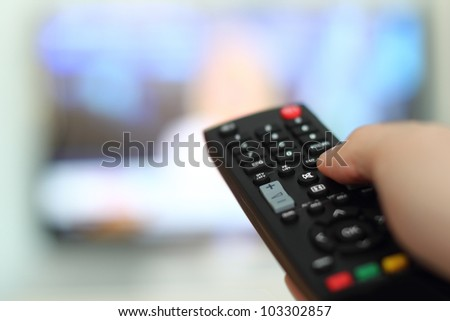 Hand holding remote control of a television - stock photo