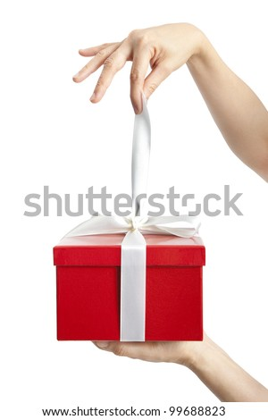 hand holding ribbon and open gift box - stock photo