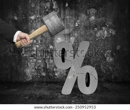 Hand holding sledgehammer hitting cracked percentage sign with dark concrete room background - stock photo