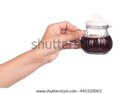 hand holding Small decanter with Soy sauce isolated on the white background - stock photo
