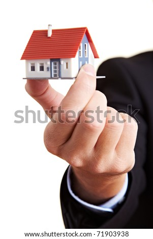 Hand holding small miniature house between the fingers - stock photo