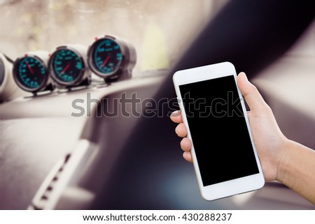 Hand holding smart phone  in car blur background - stock photo