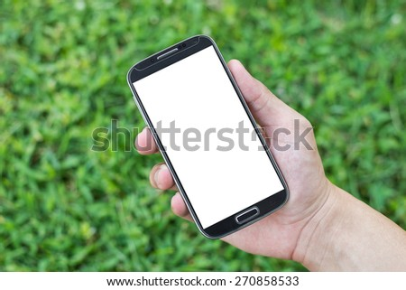Hand holding smart phone (Mobile Phone) on grass background - stock photo