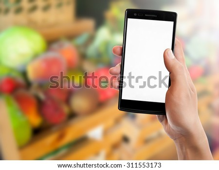 Hand holding smart phone on blured fruits and vegetables background. - stock photo