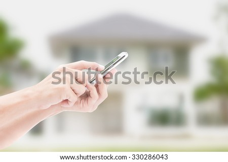 Hand holding smart phone on house backgrounds - stock photo