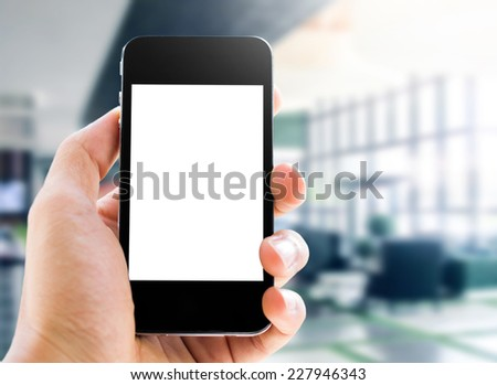 hand holding smart phone on office background - stock photo