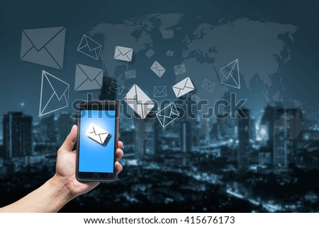 hand holding smart phone with e mail icon and city scape with world map cool tone background,networking concept,Elements of this image furnished by NASA - stock photo