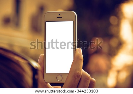 Hand holding smart-phone with white blank screen - stock photo