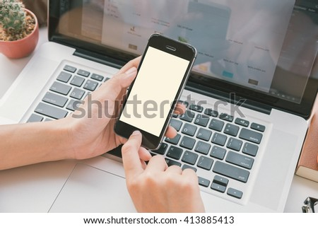 hand holding smart phone with white screen on desk office. - stock photo