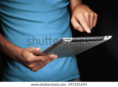 Hand holding  Smart tablet with whitescreen on black background - stock photo