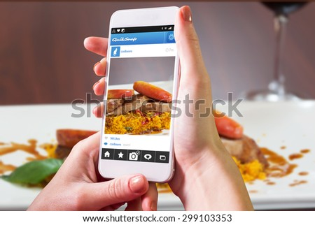 Hand holding smartphone against front view of couscous dish with meat - stock photo