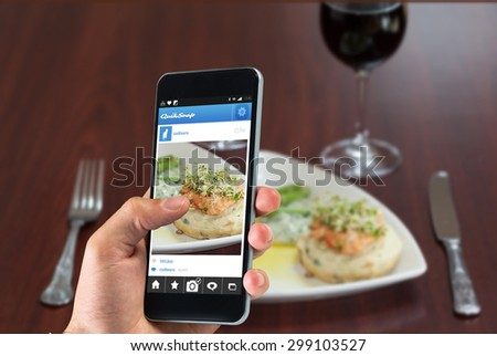 hand holding smartphone against front view of salmon dish with asparagus - stock photo