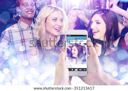 Hand holding smartphone against glowing background - stock photo