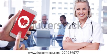 Hand holding smartphone against nurse with arms crossed - stock photo