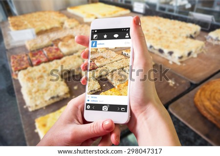 Hand holding smartphone against pastry with fruit on counter - stock photo