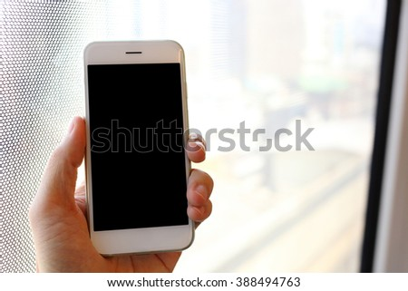 Hand holding smartphone in train - stock photo