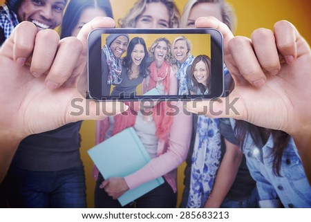Hand holding smartphone showing against cheerful group of friends laughing together - stock photo