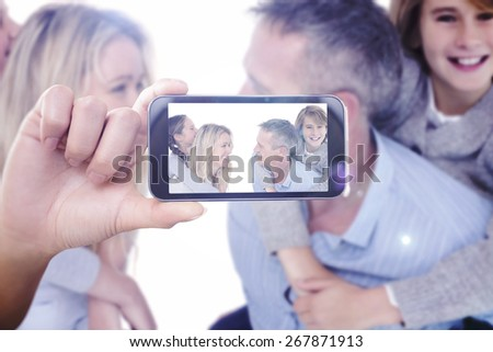 Hand holding smartphone showing against happy two parent giving their children a piggy back - stock photo
