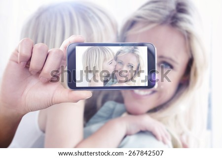 Hand holding smartphone showing against mother sitting on the couch with her daughter kissing her cheek - stock photo