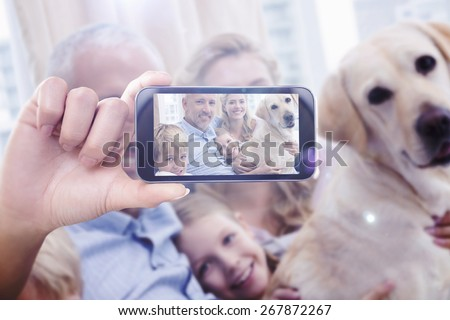 Hand holding smartphone showing against parents and their children on sofa with labrador - stock photo