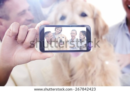 Hand holding smartphone showing against portrait of smiling family sitting together with their dog - stock photo