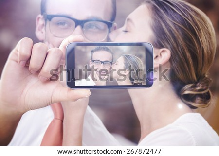 Hand holding smartphone showing against young woman kissing man - stock photo
