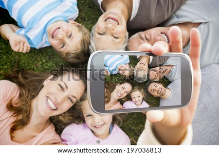 Hand holding smartphone showing extended family lying in circle at park - stock photo