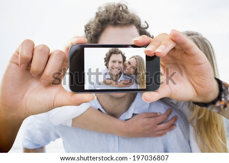 Hand holding smartphone showing man piggybacking woman at beach - stock photo