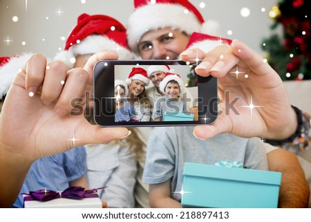 Hand holding smartphone showing photo against snow - stock photo