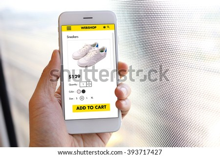 Hand holding smartphone with choose shoes on ecommerce website - stock photo