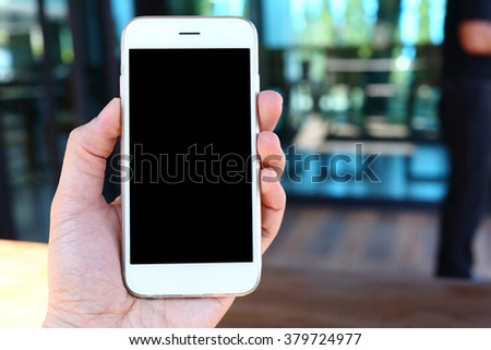 Hand holding smartphone with coffee shop background - stock photo